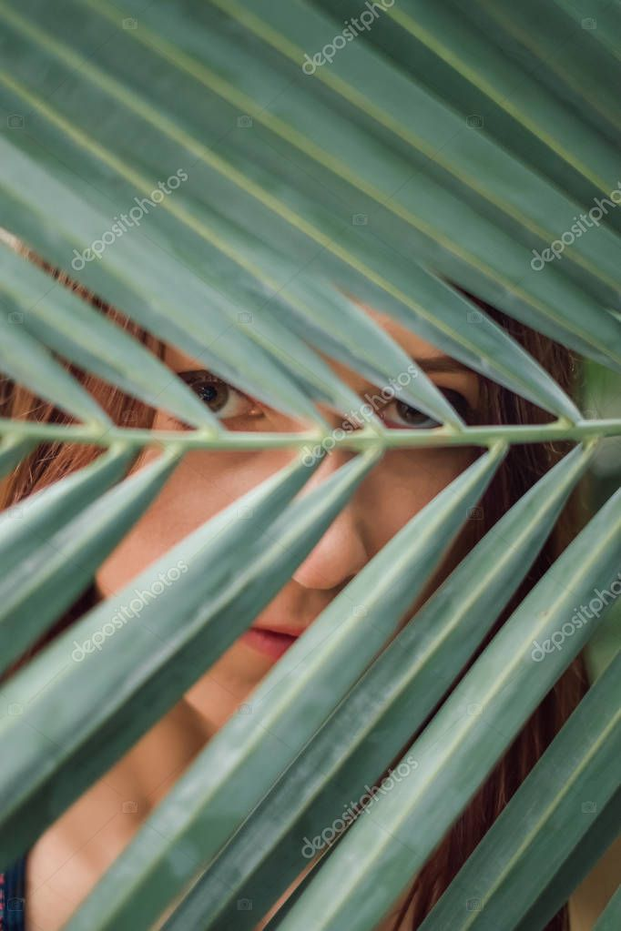 Closeup of young woman looking through palm leaf