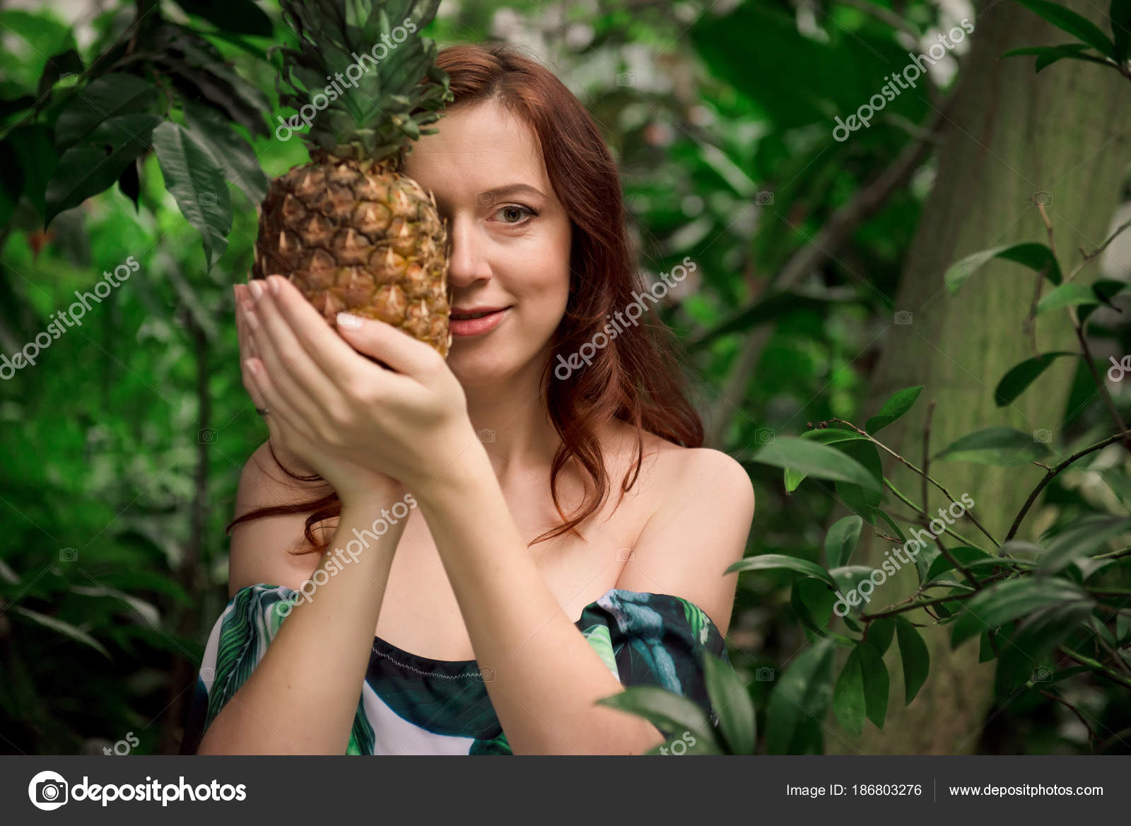 d07f705a62f41 Beautiful young caucasian woman with long red hair and bare shoulders,  holding a pineapple in her hands high up,hiding half of a face at tropical  forest.
