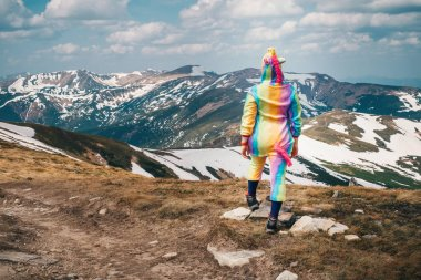 Full-length portrait shot from back of a female backpacker in a unicorn suit celebrating success,standing on top of the mountain overlooking Carpathian landscape on a Spring day. Concept of tourism.