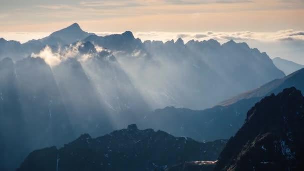 Sněžná a oblačná zimní krajina se při západu slunce propadá z Rysých vrchů, Slovensko.