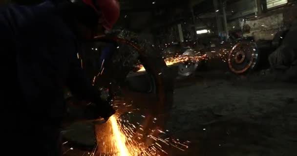 Mužské ruky uřízne kusů vodní dýmka s úhlovou brusku. Řezné oceli se mění podle přehrávané jisker na staveništi. Jiskry při řezání kovových Úhlová bruska