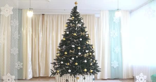 Bílý pokoj s vánoční a novoroční výzdoba. Zelený strom s hračkami a blikající věnec