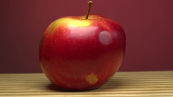 A man cuts a red Apple with a knife on a wooden Board. Close-up cutting the red apple on a wooden board. Red background