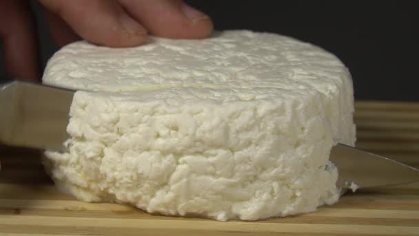 krájení měkké sýrové camembert nebo brie s nožem detailní. krémový měkký sýr uvnitř. bílé plísňové sýry s měkkou strukturou. dřevěná deska
