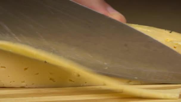 Detailní záběr kuchaře nebo kuchaře v domácnosti krájení sýra nožem, zpomalení.