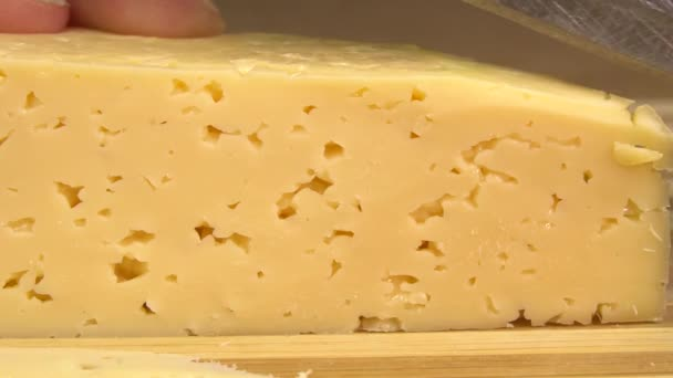 Close-up of male cook or housewife cutting cheese with a knife, slow motion.
