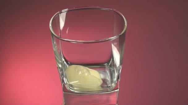 Přestaňte se hýbat a nalijte sklenici čerstvého vegetariánského jogurtu na kokosové mléko. Eko mléko v průhledném skle na bílém pozadí, izolované. Červené zrcadlo pozadí