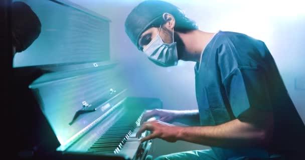 Arzt in Uniform und Maske beim Klavierspielen