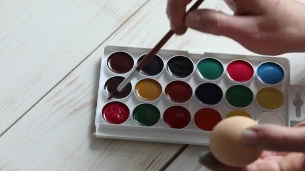 Frau malt mit roter Farbe. Palette