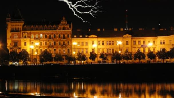 Noční scéna historické nábřeží řeky Vltavy v Praze během bouře