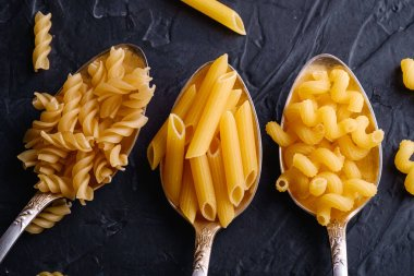 Three cutlery spoons with variety of uncooked golden wheat pasta on dark black textured background, top view macro
