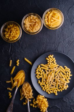 Three cutlery spoons, glass jars and plate with variety of uncooked golden wheat pasta on dark black textured background, top view