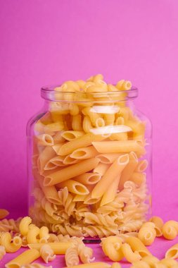 One glass jar with variety of uncooked golden wheat pasta on minimal pink background, angle view macro