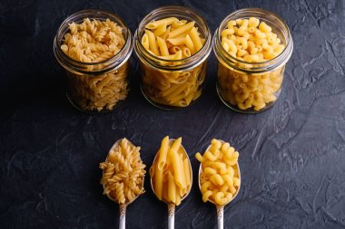 Three cutlery spoons and glass jars with variety of uncooked golden wheat pasta on dark black textured background, angle view