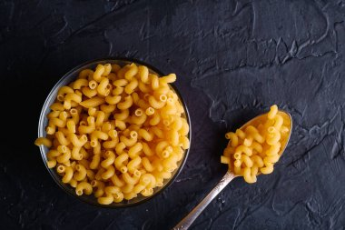 Glass bowl and vintage spoon with cavatappi uncooked golden wheat curly pasta on textured dark black background, top view