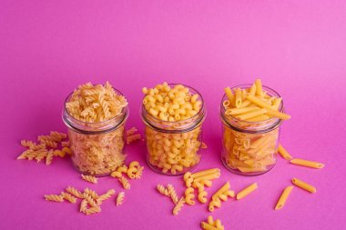 Three glass jars with variety of uncooked golden wheat pasta on minimal pink background, angle view