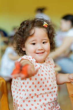kazakh curly girl playing in kids development center
