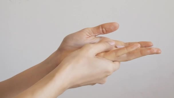 Női kéz alkalmazása kézkrém át szürke fal