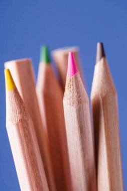 group of sharpened colorful pencils on blue background.