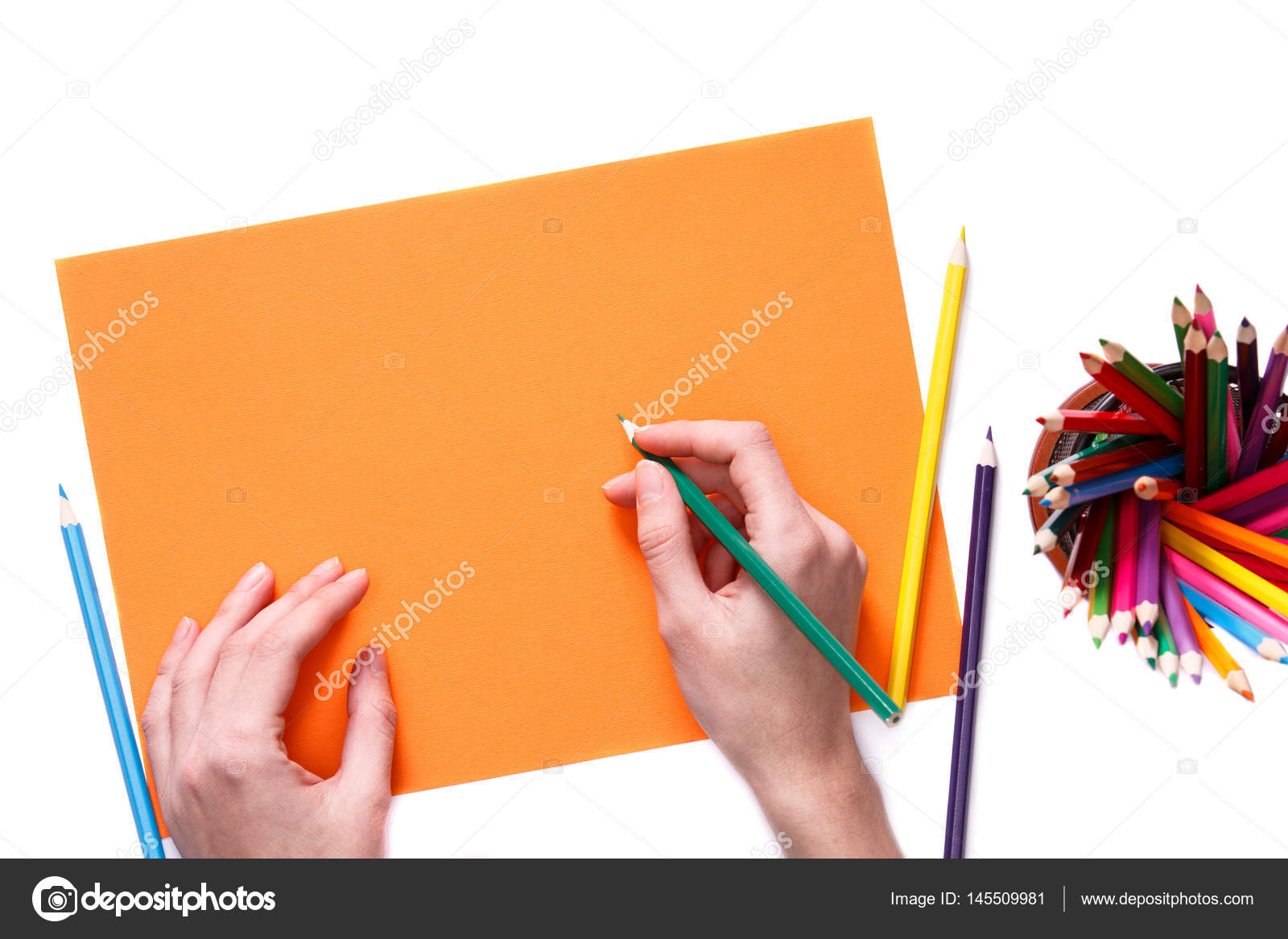 Human hands with pencil drawing something on the orange paper