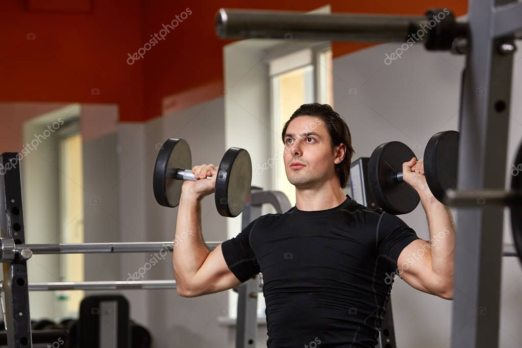 Young muscular built athlete in black sportwear working out in a gym, sitting on a weightlifting machine and lifting two dumbbells. Porttait of athlete. Horizontal photo. Healthy lifestyle.