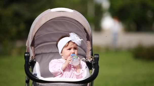 Cute baby-girl sitting in the carriage and drinking milk in the park.
