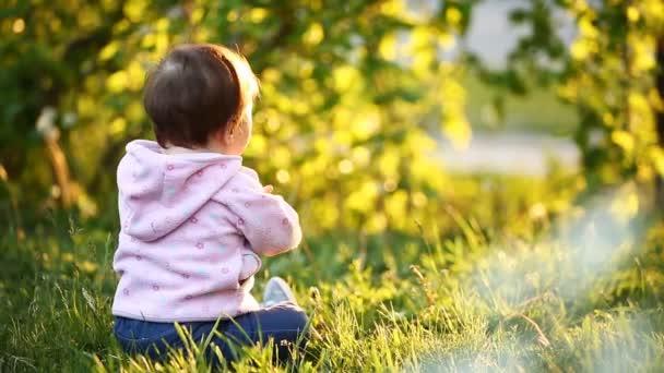 Hátulnézet a aranyos baba-lány ül a zöld fű a park ar naplemente.