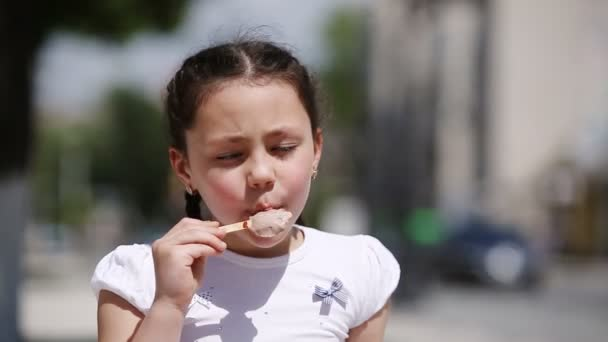 Detail roztomilá holčička jíst zmrzlinu v parku ve slunečný letní den