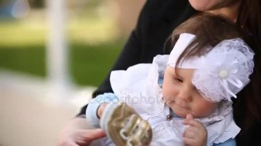 Close-up of the cute little baby-girl sitting on the arms of mother in the park.