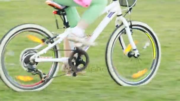 Malé radostné holčičky, jízda na kole na louce v létě ozářená den.