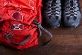Pohled shora na Turistický batoh a sportovní boty na dřevěných desek