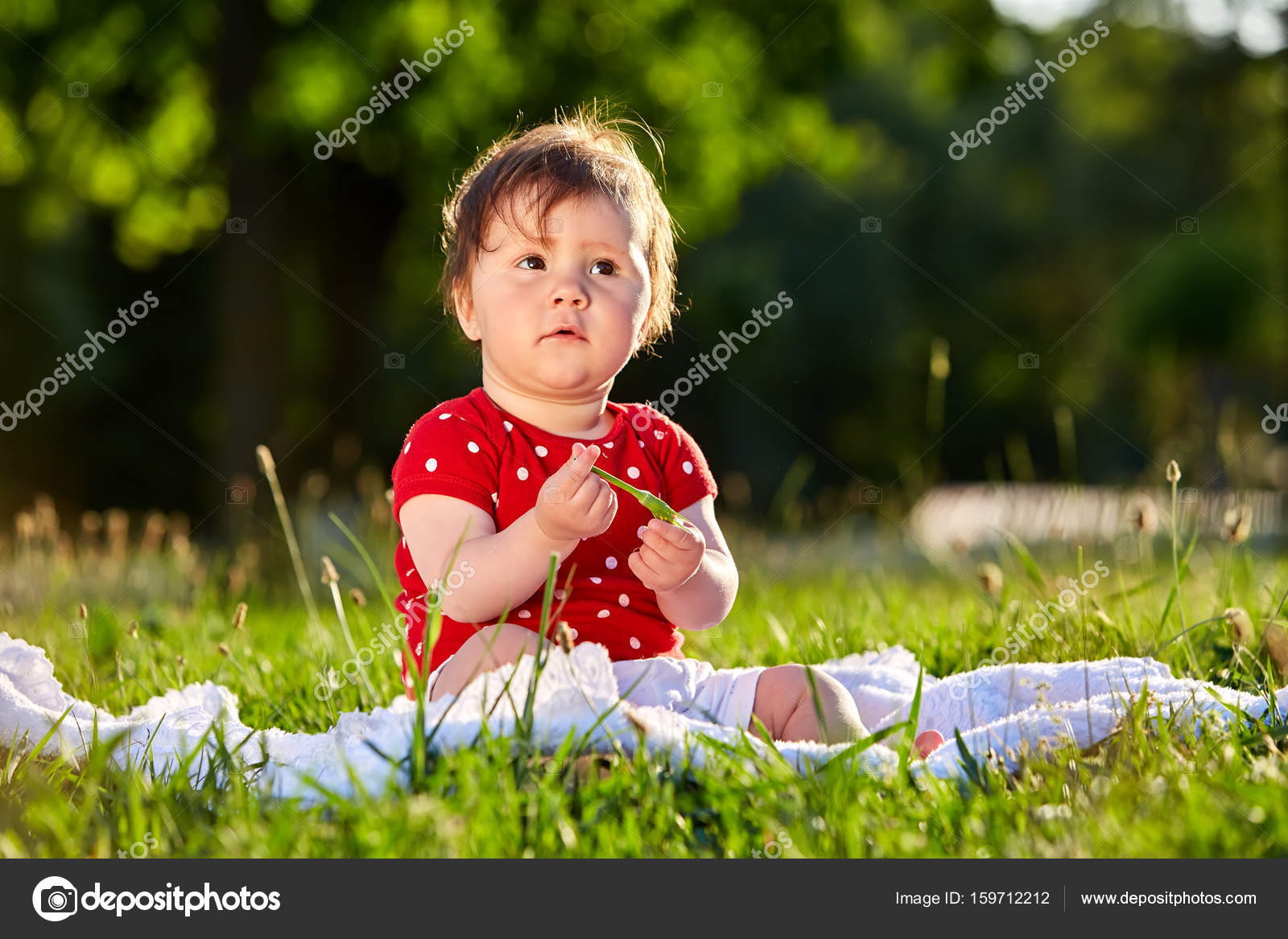 cute adorable nice baby girl in red spring dress smiling sitting