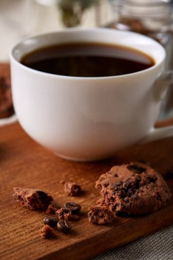Coffee cup, jar with coffee beans, cookies over rustic background, selective focus, close-up, top view