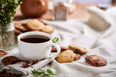 Morning coffee in white cup, chocolate chips cookies on cutting board close-up, selective focus
