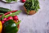 Piatto di legno con le verdure per uninsalata vegetariana su fondo strutturato bianco, primo piano, fuoco selettivo