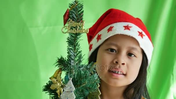 Lächelndes Mädchen mit Weihnachtsmütze, das neben dem Weihnachtsbaum liegt