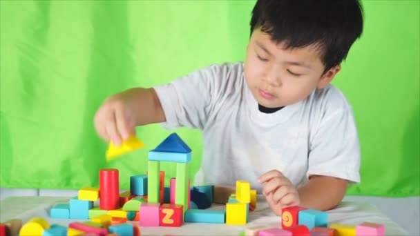 Cute boy put the colored bricks together, play indoor