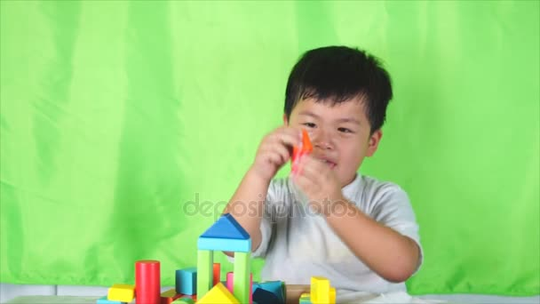 Little Cute boy put the colored bricks together, play indoor