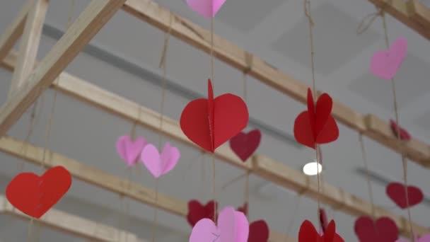 Červený papírový srdíčko visící na červeném provázku s částicemi srdce