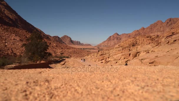 People walking along the road between the desert mountains