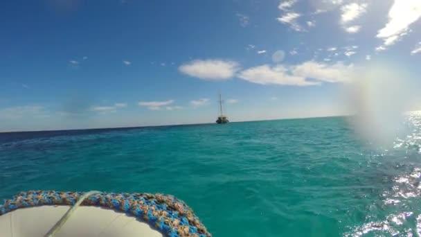 Motorový člun pluje na moři. Na obzoru je vidět jachta