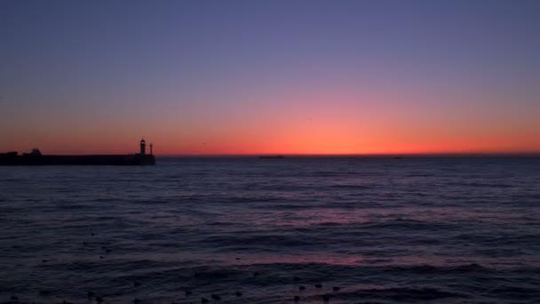 Molo s majákem na obloze za svítání