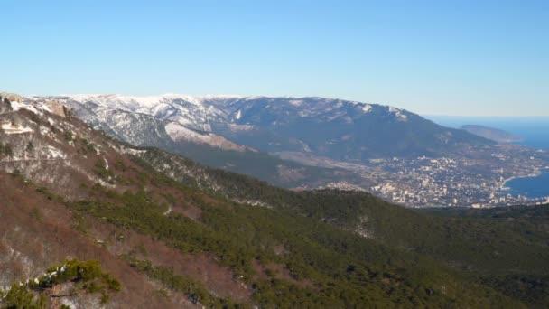 Pohled na vrcholky zasněžených hor. V údolí můžete vidět město Jalta