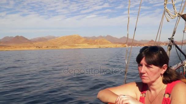 Mladá žena sedí na palubě jachty