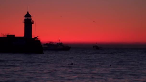 Obrysy Krtek s majákem a loď na pozadí dawn