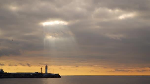 Paprsky slunce přes zamračená obloha při západu slunce