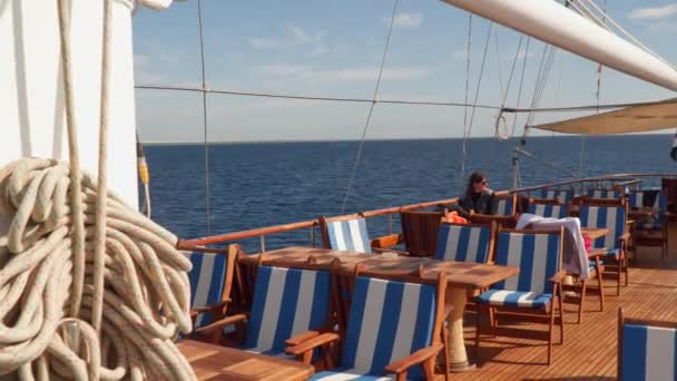 Žena sedí u stolu na otevřené palubě jachty plachetnice