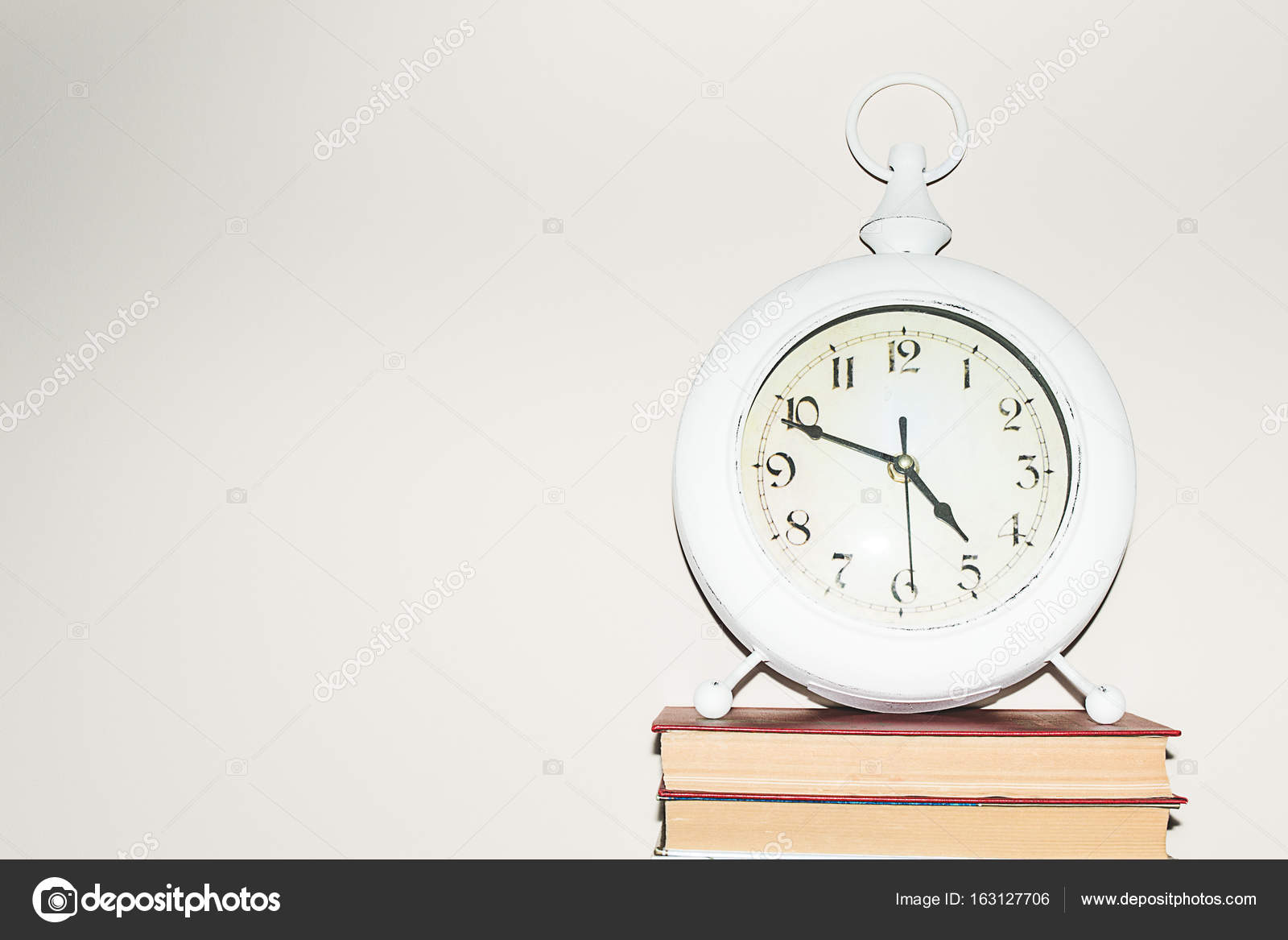 Still life round clock on stack of books. Education and learning ...
