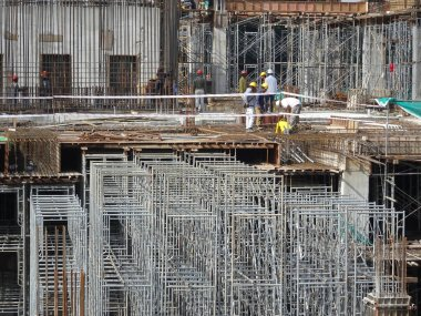 KUALA LUMPUR, MALAYSIA -JULY 07, 2017: Construction workers working at height at the construction site. Using scaffolding as the temporary platform to work. They are required to wear proper safety gear.