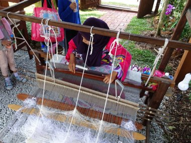 KUALA LUMPUR, MALAYSIA -SEPTEMBER 6, 2017: A woman is using traditional weaving machines to weave songket. Songket is a Malay traditional clothes with high quality and value.